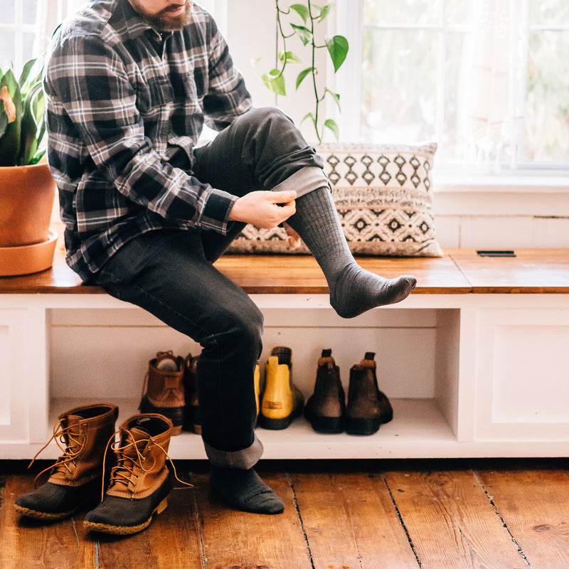 Man sitting on a wooden bench in his house, puling up his socks, wearing The Standard Mid-Calf Lightweight Lifestyle Sock in Medium Gray, Lifestyle Image