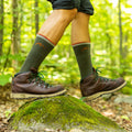 Man hiking in the forest, stepping over a rock wearing hiking boots and Coolmax Hiker Boot Hiking socks in gray/black, Lifestyle Image