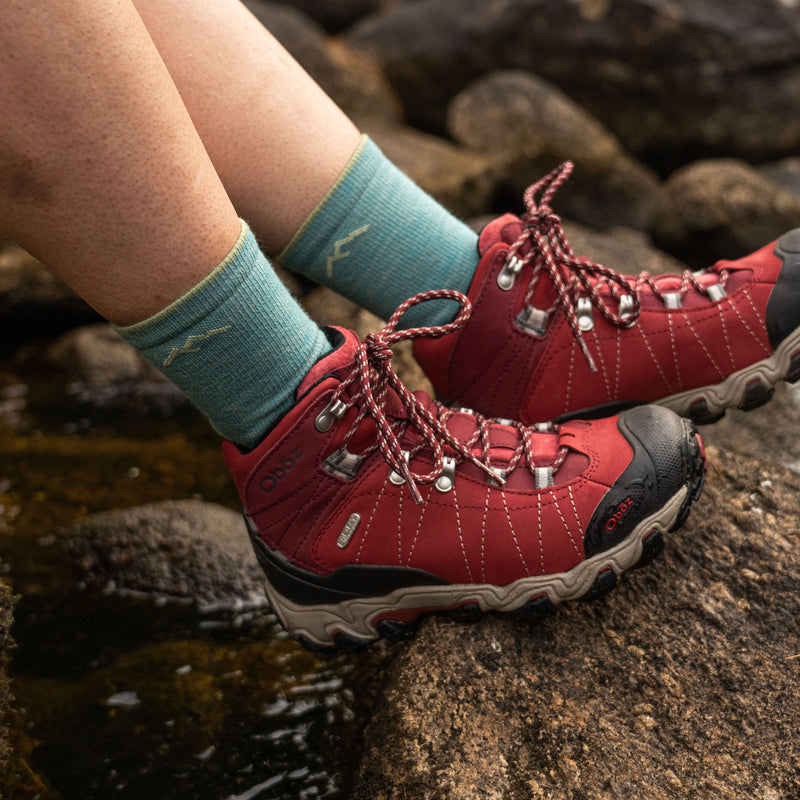 Close up image of a woman's feet, wearing Women's Light Hiker Micro Crew Hiking Socks in Aqua with red hiking boots, Lifestyle Image