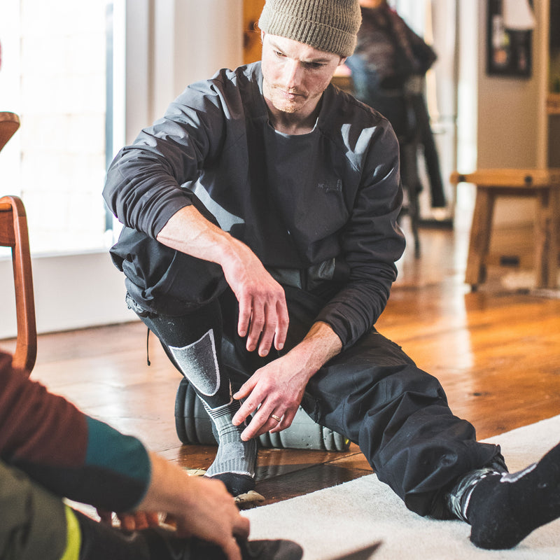 Man sitting on the floor in snow gear, getting ready to go, wearing Function 5 Over the Calf Ski & Snowboard socks in Black, Lifestyle Image