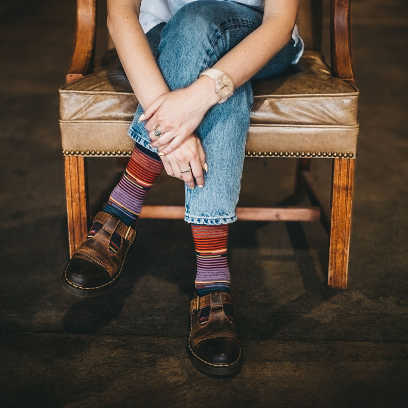 Image of a woman's legs, crossed, sitting in an old leather and wood chair wearing shoes and Women's Pixie Crew Lightweight Lifestyle Socks in Navy, Lifestyle Image