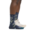 Profile image of a woman's legs on a white background facing to the right, wearing Women's Folktale Crew Lightweight Lifestyle Socks in Denim with back foot also in a white Converse sneaker
