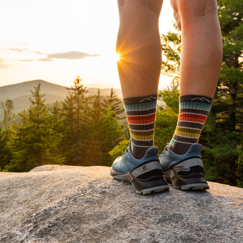 A woman stands on a rock wearing sneakers and Women's Decade Stripe Micro Crew Midweight Hiking Socks in Taupe, looking out over a forest and mountain range as the sun sets, Lifestyle Image
