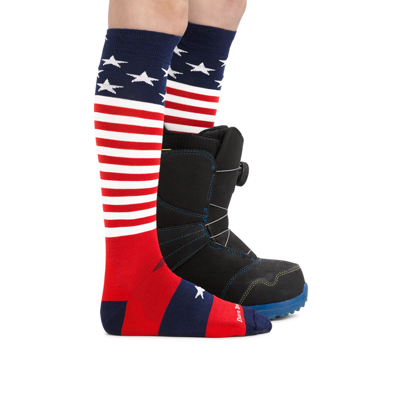 Profile image of kid legs facing to the right wearing Captain Stripes Over the Calf Lightweight Ski & Snowboard in Stars and Stripes with rear foot in a snowboard boot