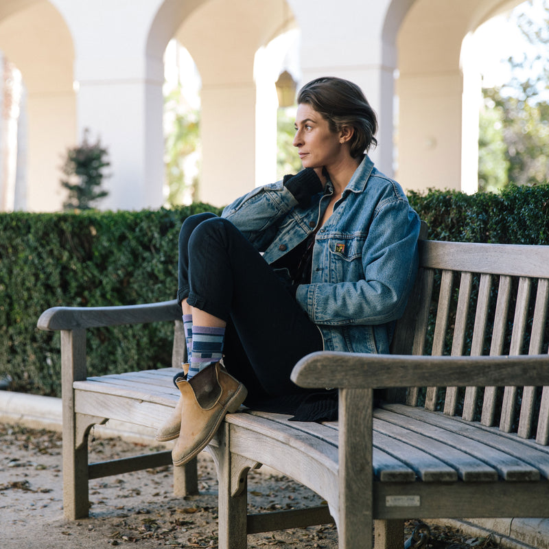 Woman sitting on a park bench, wearing a jean jacket, black pants and casual boots with Women's Alexa Crew Lightweight Lifestyle Socks in Denim, Lifestyle Image