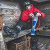 Lifestyle image of a man sitting on a wooden bench pulling up his Outer Limits Over the Calf Lightweight Ski & Snowboard Socks in Gray, getting ready to go snowboarding, Lifestyle Image