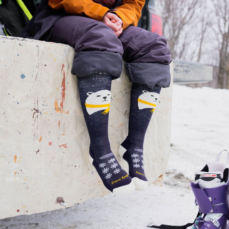 Image of a woman sitting on a concrete wall wearing snowpants rolled up to the knee and wearing Women's Mama Bear Over the Calf Midweight Ski & Snowboard Socks in Blue, Lifestyle Image