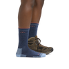 Profile image of a woman's legs on a white background, facing to the right, wearing Women's Hiker Boot Midweight Hiking Socks in Denim with Cushion and a hiking boot on one foot