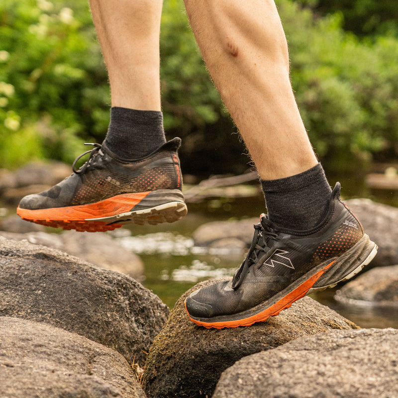 Close up lifestyle image of a man stepping over rocks in a stream wearing sneakers and Light Hiker Quarter Lightweight Hiking Socks in Black, Lifestyle Image