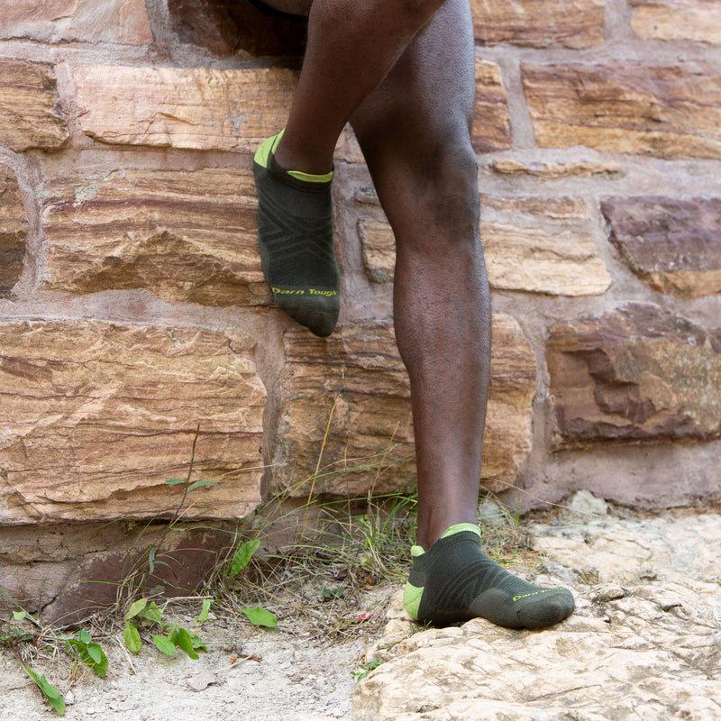 Man leaning against a wall, wearing running shorts and Men's Run No Show Running Socks in Fatigue, Lifestyle Image