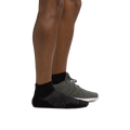 Profile of male legs facing right wearing Coolmax Run Quarter Ultra-Lightweight Running Sock in Black with back foot in a running shoe