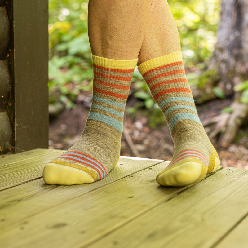 Close up image of a woman's feet, legs crossed, standing on a wooden porch while wearing Women's Gatewood Boot Midweight Hiking Sock in Oatmeal, Lifestyle Image