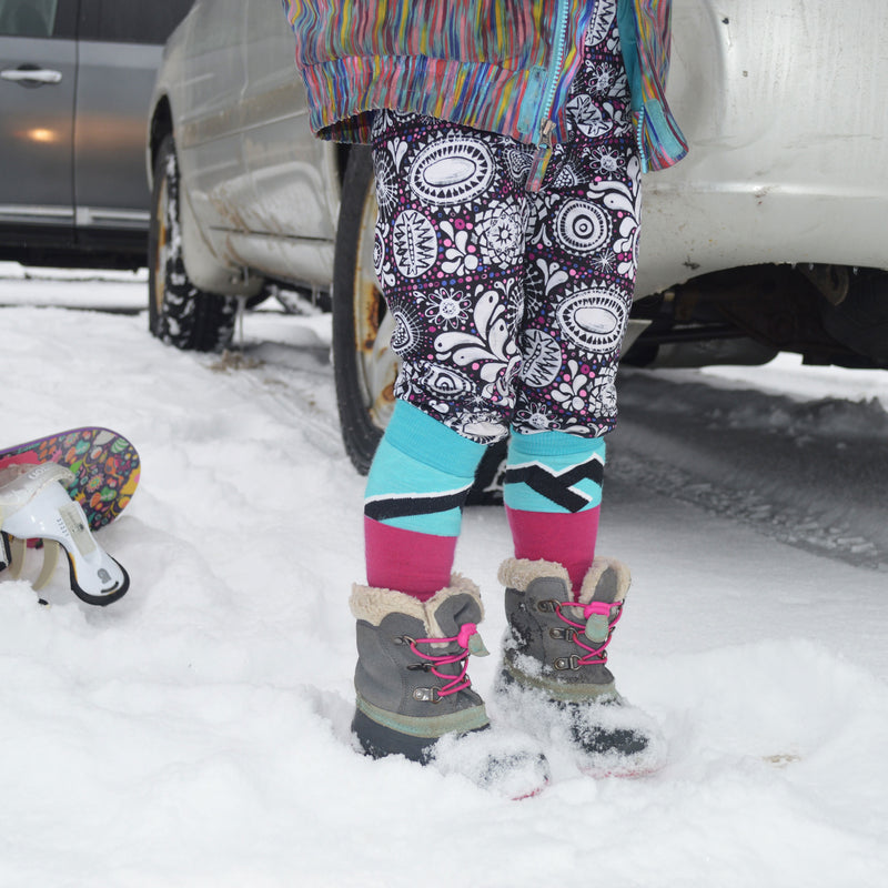 Little girl standing in the snow in snow boots, wearing Mountain Top Over-the-Calf Ski & Snowboard socks in pink pulled up to her knees, over her colorful pants, Lifestyle Image