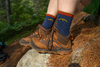 Image of two feet resting on a rock in the woods wearing hiking boots and the 1466 hiker micro crew sock in denim blue, Lifestyle Image