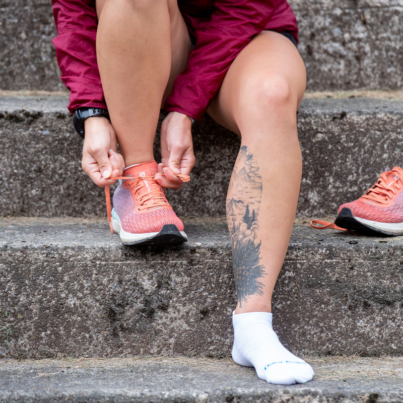 Woman sitting on concrete steps putting on running shoes wearing Women's Coolmax Run No Show Running Socks in White, Lifestyle Image