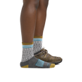 Profile image of a woman's legs on a white background, facing right, wearing Women's Sobo Micro Crew Lightweight Hiking Socks in Gray with one foot also wearing a hiking boot