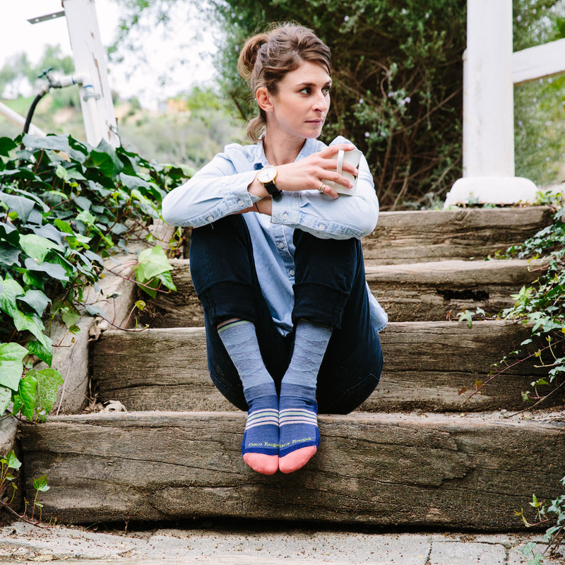 A woman sits on wooden steps, outside, holding a mug and wearing Women's Waves Crew Lightweight Lifestyle Sock in Denim, Lifestyle Image