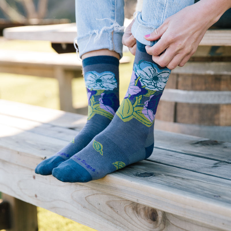 Image of a woman's feet on a wooden bench wearing Women's Watercolor Crew Lightweight Lifestyle Socks in Slate, Lifestyle Image