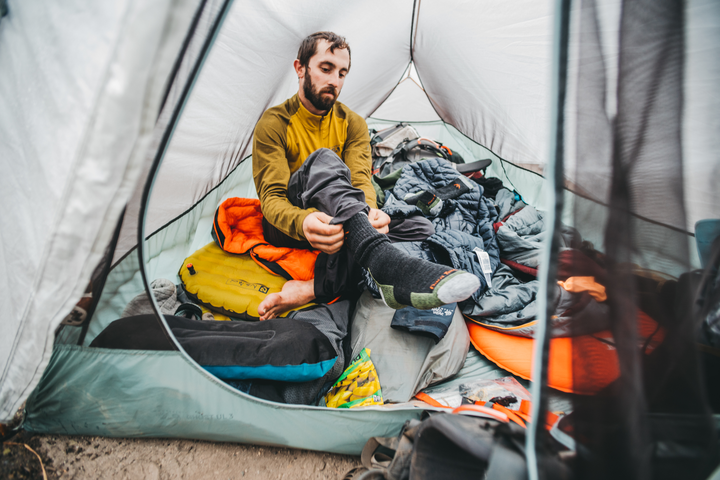 Backpacker sitting in his tent getting ready for the day by pulling on darn tough 1403 hiker boot men's socks in lime green and black. Lifestyle Image