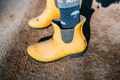 Close up of a woman's feet in yellow rainboots wearing Women's Umbrellas Crew Lightweight Lifestyle Sock in Denim, Lifestyle Image