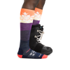 Profile image of a woman's legs facing to the right on a white background wearing Women's Snowflake Over the Calf Midweight Ski & Snowboard Socks in Sunset with one foot also in a snowboard boot