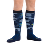 Kid standing barefoot with feet pointing outward so that the yetis in the camo pattern on the inside of the shins is visible on Camo Over the Calf Midweight Ski & Snowboard Socks in Eclipse