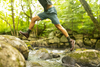 Hiker leaping from one rock to another to cross a stream in the woods. Wearing shorts, hiking boots, and darn tough micro crew socks for hikers in Olive. Lifestyle Image
