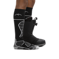 Man facing to the right, wearing Function 5 Over the Calf Ski & Snowboard Socks in Black, back foot also wearing a snowboard boot