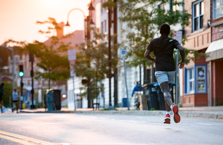 Lifestyle image of a man running down a city street, wearing Run Quarter Ultra-Lightweight Running Socks in White, Lifestyle Image