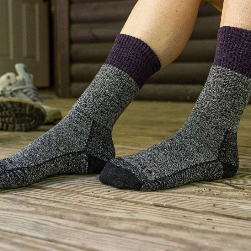 Close up of a woman's feet resting on a wooden porch wearing Women's Scout Boot Midweight Hiking Socks in Plum, Lifestyle Image
