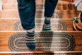 Close up perspective lifestyle image of a man walking up wooden stairs with stair rugs on them wearing Static Crew Lightweight Lifestyle socks in midnight, Lifestyle Image