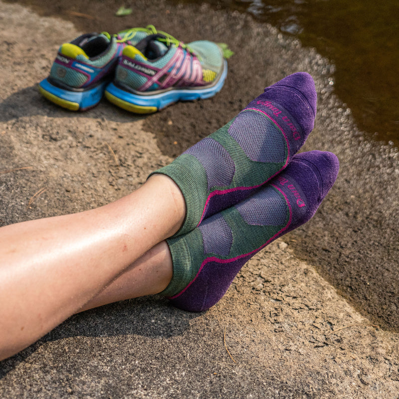 Close up image of a woman's feet, ankles crossed on a rock, barefoot and wearing Women's Light Hiker No Show Lightweight Hiking Socks in Moss Heather, Lifestyle Image