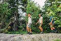 Image of 3 men walking along a rock ledge in a forest, each wearing 3 different heights of hiking socks - no show, quarter, and micro crew, Lifestyle Image