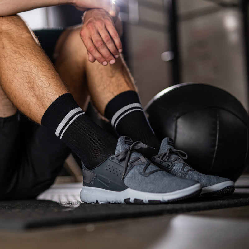 Close up lifestyle image of a man sitting on the floor of a gym next to a medicine ball wearing athletic sneakers and Element Crew Lightweight Athletic Socks in Black, Lifestyle Image