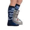 Profile of kid legs facing to the right wearing Camo Over the Calf Midweight Ski & Snowboard Socks in Eclipse and a ski boot on the foot in the back