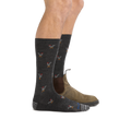 Profile of male legs facing right wearing  Strut Crew Lightweight Lifestyle Socks in Charcoal and back foot also wearing a casual boot