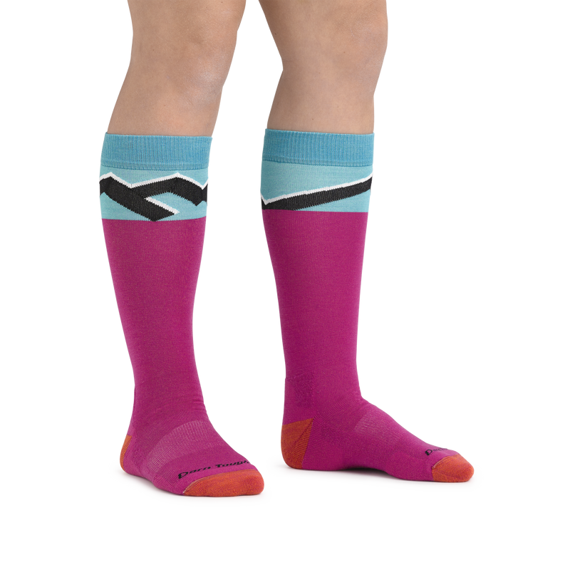 Kid standing barefoot wearing Kids Mountain Top Over the Calf Midweight Ski & Snowboard Sock in Pink