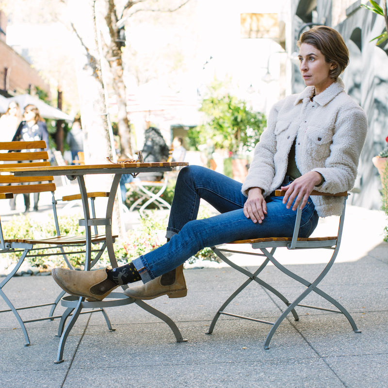 Image of a woman sitting at a table outside, legs extended wearing rolled up jeans and boots with Women's Folktale Crew Lightweight Lifestyle Sock in Charcoal exposed, Lifestyle Image