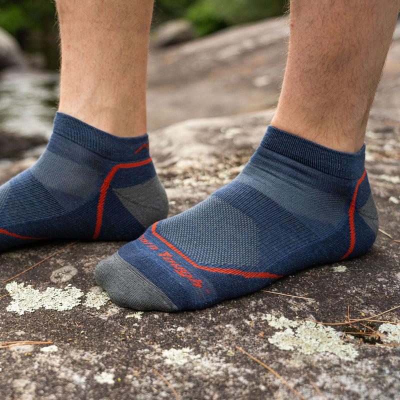 Close up lifestyle image of a man's feet, standing on a rock wearing only Light Hiker No Show Lightweight Hiking socks in Denim, Lifestyle Image
