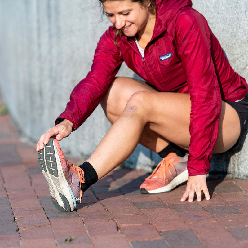 Image of a woman crouching down, stretching, wearing running shoes and Women's Run 1/4 Running Socks in Black, Lifestyle Image
