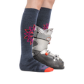 Profile image of a woman's legs on a white background, facing right, wearing Women's Sacred Over the Calf Midweight Ski & Snowboard Socks in Denim with one foot in a ski boot