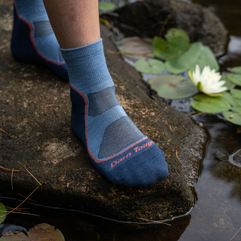 Close up image of a woman's foot on a rock, surrounded by water and lily pads wearing Women's Light Hiker Quarter Lightweight Hiking Socks in Denim, Lifestyle Image