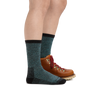 Profile image of a woman's legs on a white background wearing Women's Nomad Boot Midweight Hiking Socks in Aqua with one foot in a hiking boot