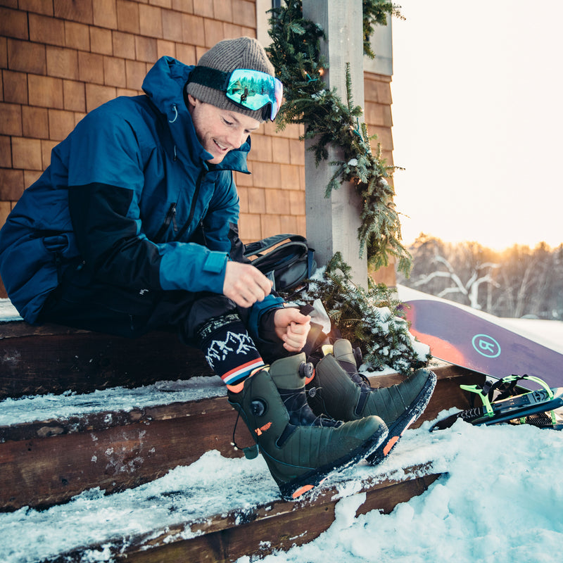 Man sitting outside on snow covered steps, lacing up his snowboard boots while wearing Alpenglow Over the Calf Ski & Snowboard socks in Red, Lifestyle Image