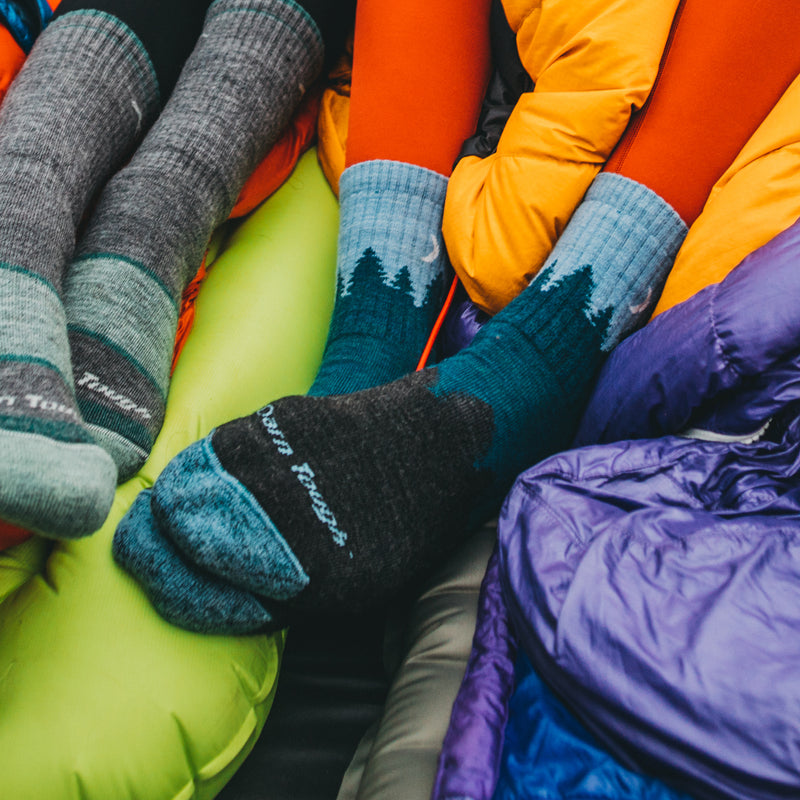 Close up image of women's feet on top of sleeping bags in a tent, one woman wearing Women's Treeline Micro Crew Hiking socks in Blue, Lifestyle Image