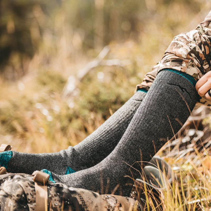 Image of a woman's legs in field, wearing camo hunting gear and pulling up her Women's Mountaineering Over the Calf Heavyweight Hiking Socks in Midnight, Lifestyle Image