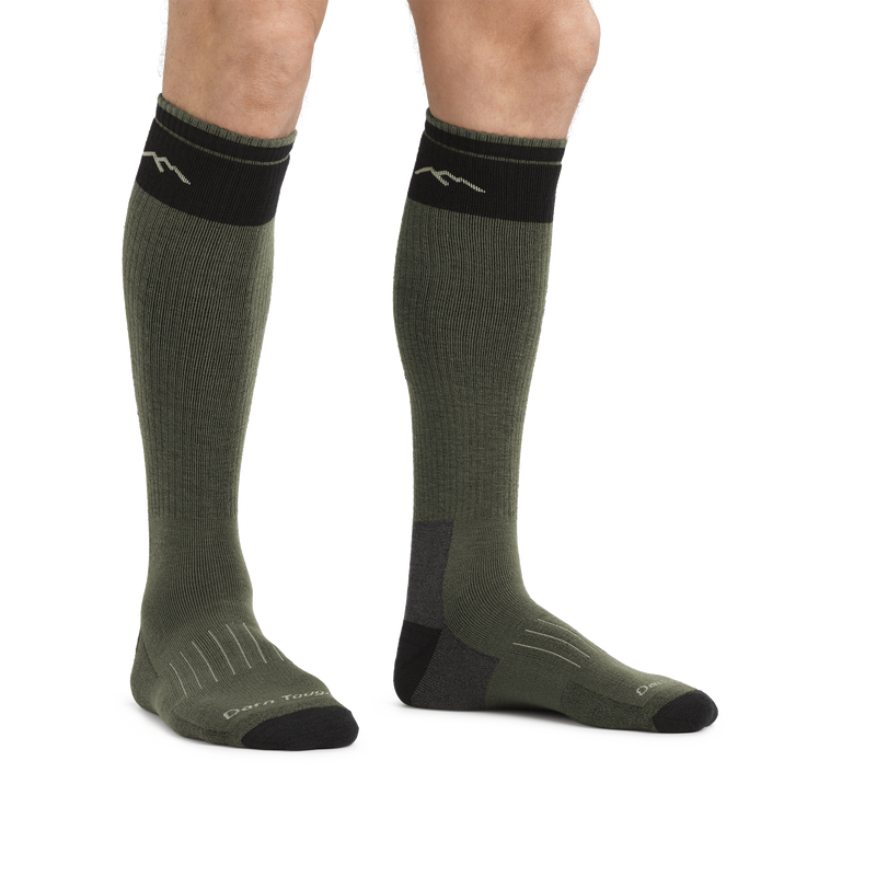 Man standing barefoot against a white background wearing Hunter Over the Calf Heavyweight Hunting Socks in Forest