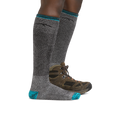 Profile image of a woman's legs on a white background, facing right, wearing Women's Mountaineering Over the Calf Heavyweight Hiking Socks in Midnight with one foot also in a hiking boot