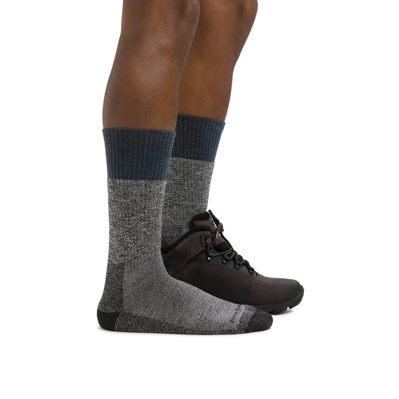 Profile of male legs facing right wearing Scout Boot Midweight Hiking Socks in Denim and a hiking boot on the foot in back