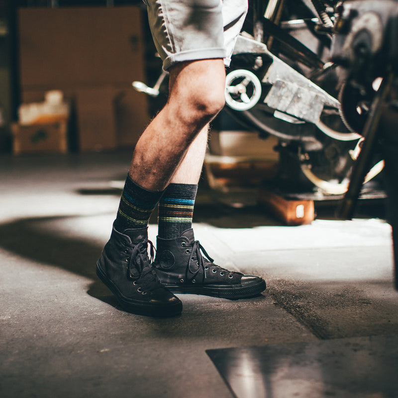 Waist down image of a man, standing in a garage wearing shorts and working on engines wearing DT Train Crew Lifestyle Sock in Charcoal, Lifestyle Image